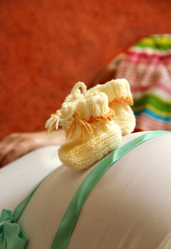 Pregnant woman tummy and small cute baby socks