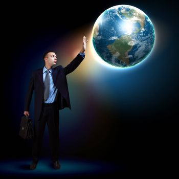 Businessman standing with our planet Earth. Elements of this image are furnished by NASA