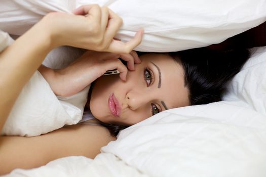 Beautiful woman with cell phone making call in bed hiding with pillow