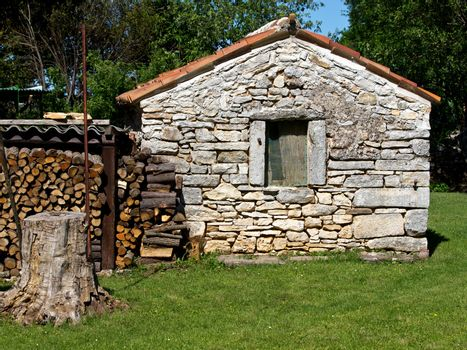 old small stone house with fire wood