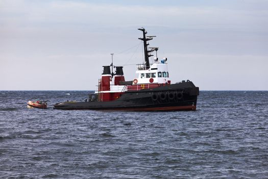 Tugboat floating in wait on calm ocean at anchor
