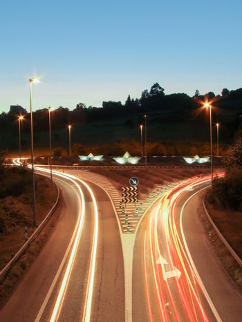 Car light trails on the road and paper boats in a roundabout