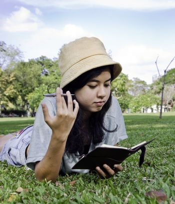 Young beautiful asian woman lies on green summer meadow with book
