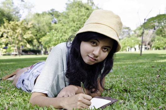 Young beautiful woman lies on green summer meadow with book