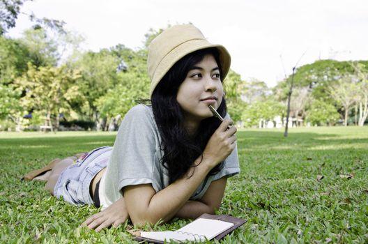 Woman thinking hard studying outside. Beautiful mixed asian / caucasian woman.