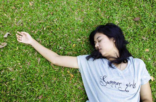 Young beautiful asian laying on the grass, in the park