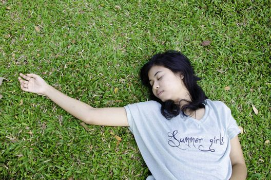 Young asian model laying in the grass