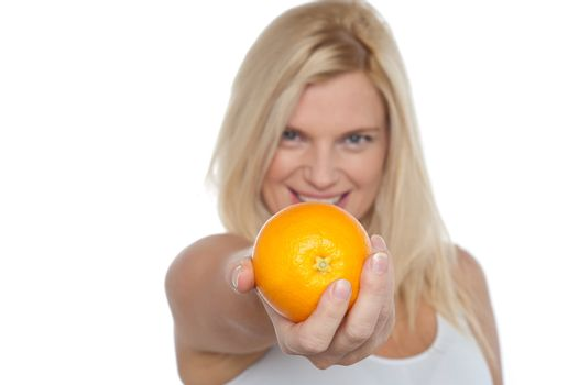 Gorgeous woman with an orange in her outstretch arm