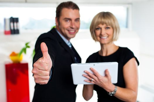 Secretary with a tablet posing with her successful boss