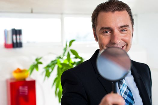 Business executive holding magnifying glass