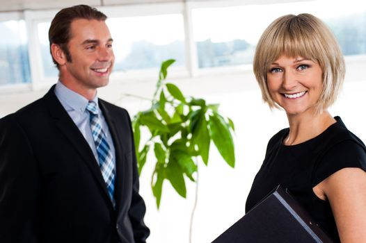 Handsome boss passing by smiling female colleague
