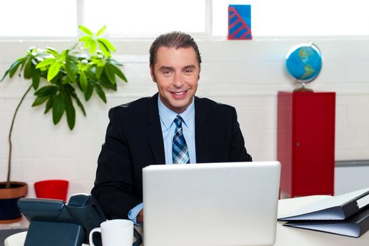 Corporate leader sitting in front of his laptop