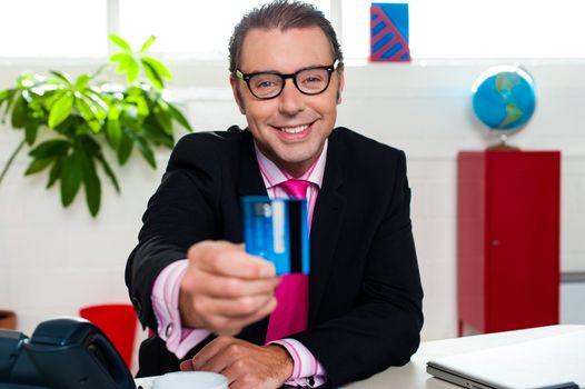 Smiling business executive displaying credit card
