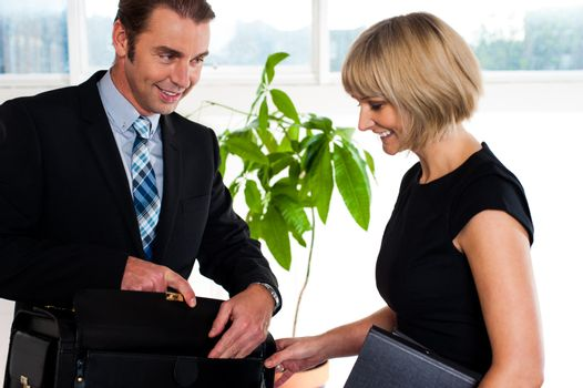 Boss opening his briefcase in front of secretary