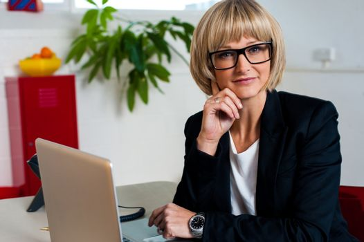 Thoughtful business lady seated in office