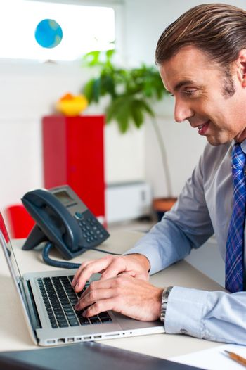Businessman typing report on a laptop