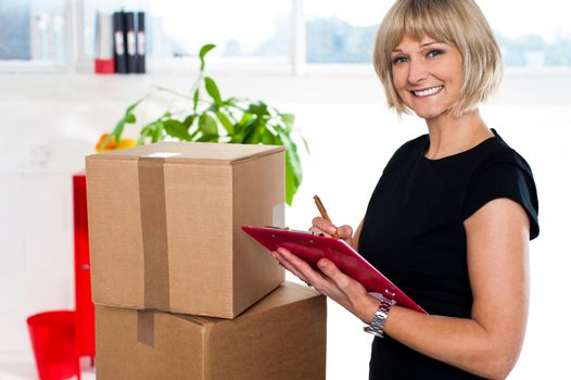 Casual woman documenting list of goods on clipboard