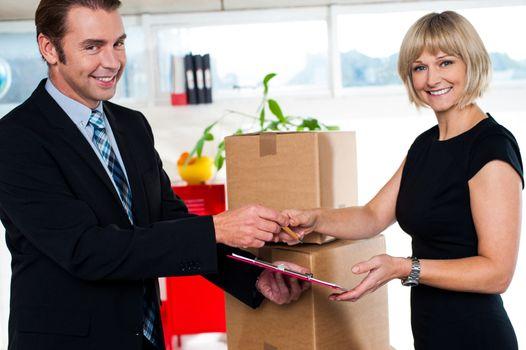 Boss handing over signed document to his secretary