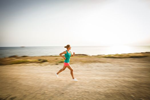Young woman on her evening jog along the seacoast (motion blurre