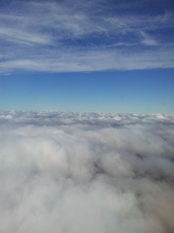 Aerial view of white clouds from airplane window.