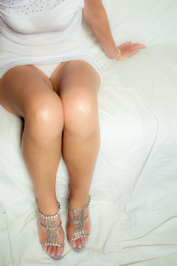 Sexy woman's legs sitting on a white sofa, luxury dressed