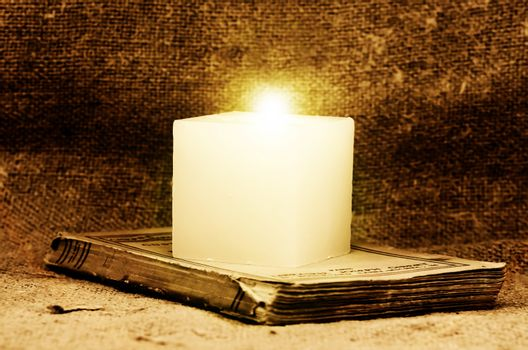 candle on an old book