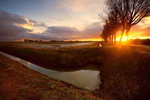 sunrise in farmland by canal