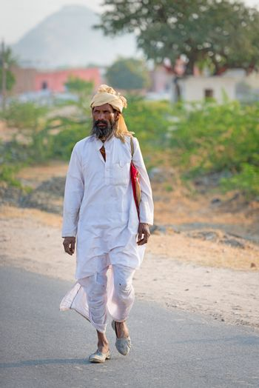 Sambhar, India - Nov 19: Indian countryman in traditional white cloth passes country road on Nov 19, 2012 in Sambhar Salt Lake, Rajasthan, India.