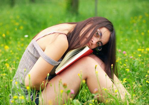 Young  female student holding a book  over nature background