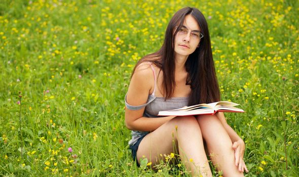 Young  female with a book  on a green meadow