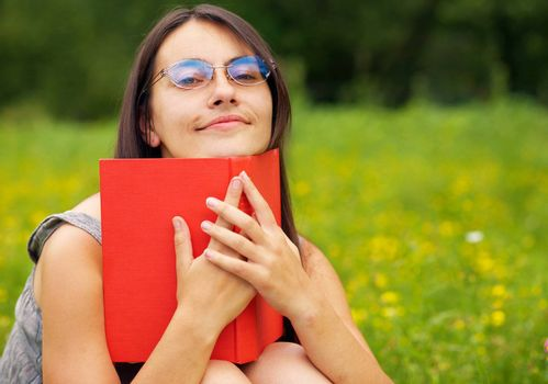 Closeup portrait of a young  female with a book  on a green meadow