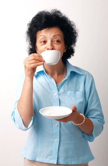 Portrait of an elder woman drinking from a cup and holding a saucer.