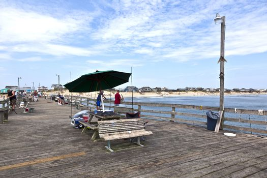 NAGS HEAD, USA - JUL 18.: people enjoy fishing at the famous pier on July 18,2010 in Nags Head, USA. The first oceanfront cottage was built here around 1855 by Dr. W.G. Pool and the lenght of the pier is 750 ft.