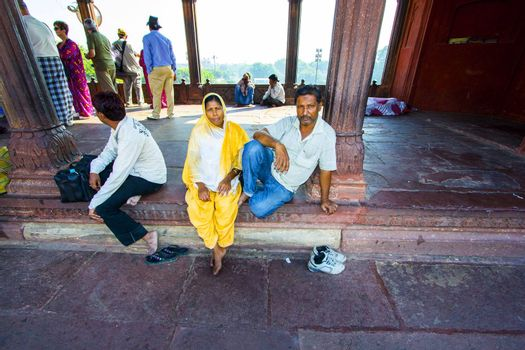 DELHI, INDIA - OCTOBER 16: A family of worshipers rest on the courtyard of Jama Masjid Mosque on October 16, 2012 in Delhi, India. Jama Masjid is the principal mosque of Old Delhi in India.