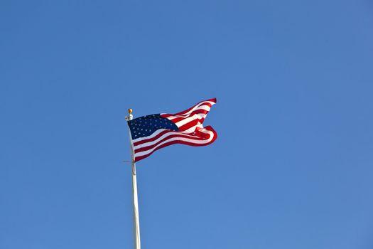 American flag waving against a brilliant blue sky