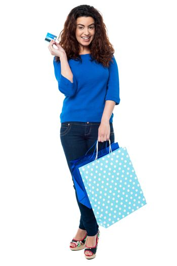 Shopaholic woman holding shopping bags and credit card
