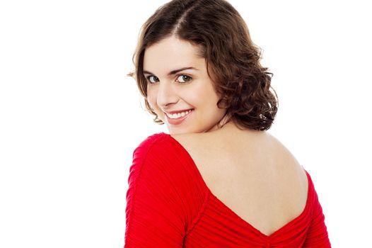 Flirtatious female turning back and passing smile