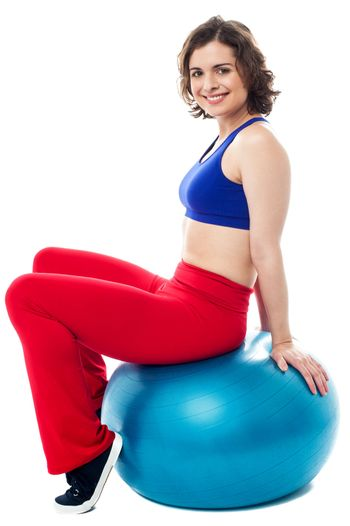 Woman relaxing on big exercise ball after workout