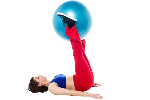 Fit woman holding exercise ball between legs