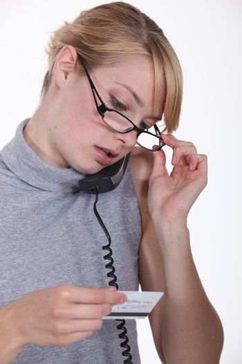 secretary holding a visit card and calling someone