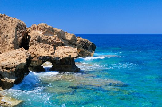 Rocky shore of the Mediterranean sea with clear water.