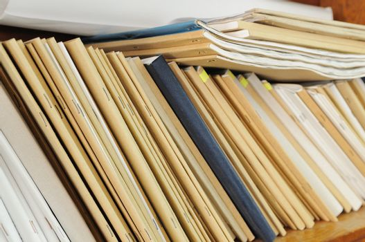 Wooden shelf with file folders, archival documents.