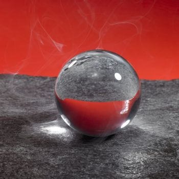 a clear crystal ball on rough dark grey stone surface in front of red back, little smoke around