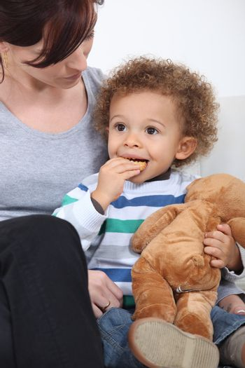 Mother sat with toddler eating biscuits