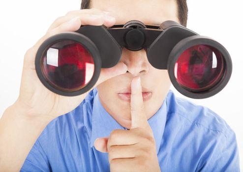 man looks through binoculars with silent gesture
