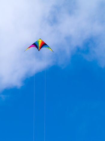 A rainbow colored stunt kite against a blue sky with wispy clouds.
