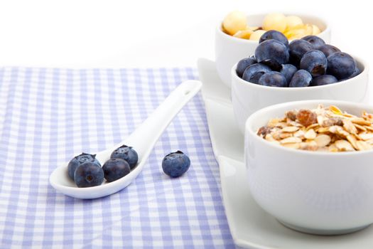 fresh blueberry in white porcelain spoon with bowl of cornflakes