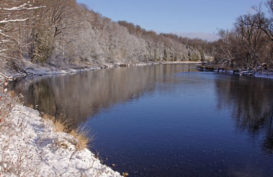 The Grand River with snow covering the banks.  Shot in Kitchener, Ontario, Canada.
