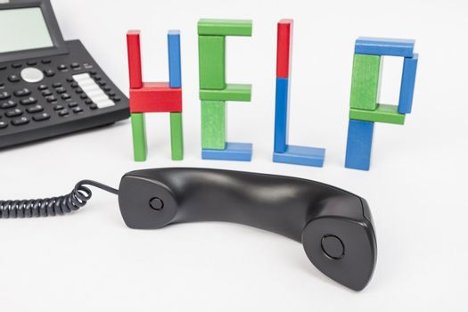 the word help made with toy bricks and a phone in background. telephone receiver in the foreground
