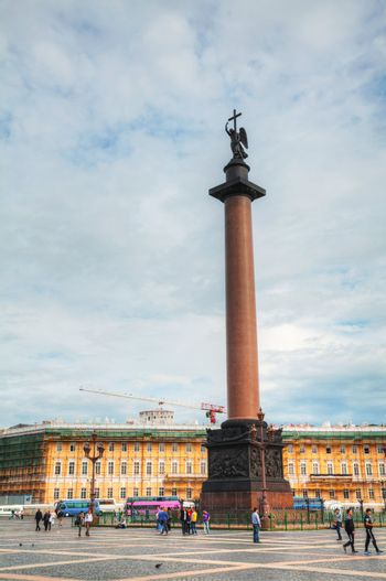 SAINT PETERSBURG, RUSSIA - AUGUST 25: The Alexander Column at Palace (Dvortsovaya) Square in St. Petersburg, Russia on August 25, 2012 with tourists. The monument was erected after the Russian victory in the war with Napoleon's France.